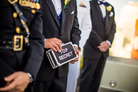 "man in suit holds a black box that says ""top secret"""